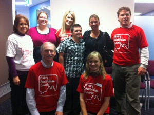 Eight people - four men and four women - standing some wearing red Every Australian Counts tshirts